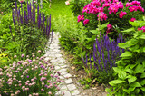 Fototapety Lush blooming summer garden with paved path