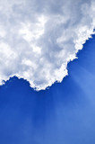 Blue sky with sunrays shining from behind the clouds poster