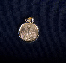 A gold liberty coin in a pendant on a black background