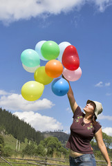 girl playing with color balloons