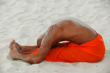 Tanned white man practicing yoga on the beach