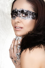 Masked beauty with silver leaf and feather boa