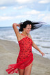 Beautiful happy woman dancing on the beach