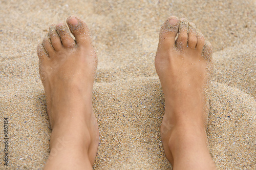 feet in the sand of the beach