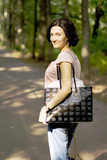 happy brunet woman with shopping bag, outdoors poster