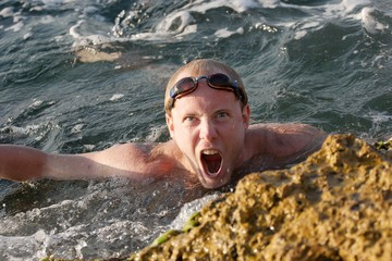 Roaring man swimming in the waves