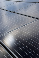 Sun reflecting on roof mounted solar energy panels