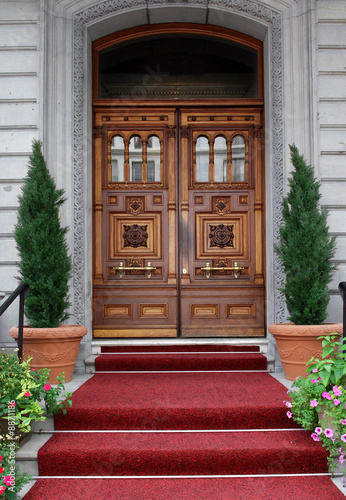 elegant club entrance with oak door and flower pots