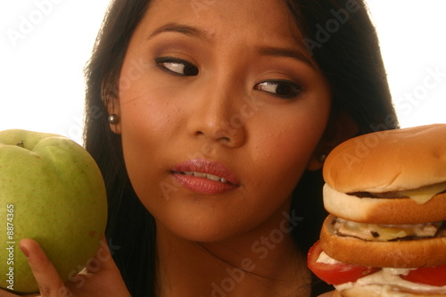 Woman choosing burger and apple