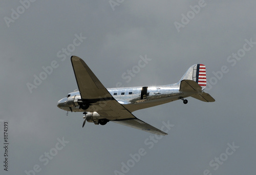 Vintage silver airplane in flight with open side door