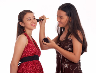 young teenager applying a blush-on to her friend