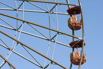 detail from big ferris wheel at amusement park and blue sky