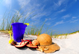 Pretty array of beach accessories on sand dune poster