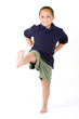 Happy mixed race boy with hands on hips and kicking a leg