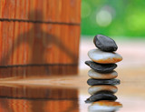 Shadow of woman doing yoga on fence by stacked smooth stones poster