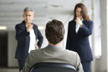 Two businesswomen interrogating a man.