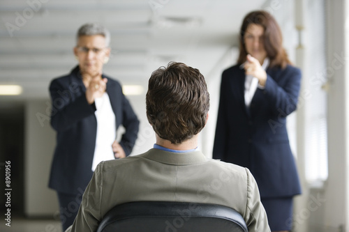 Two businesswomen interrogating a man.