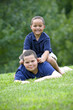 Two brothers playing on fresh green grass