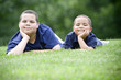 Two brothers lying on their fronts on fresh green grass