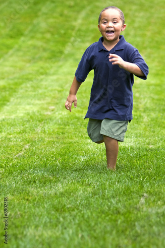 Happy mixed race boy running through green grass