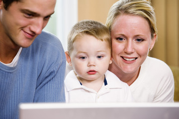 View of parents teaching their son to use a computer.