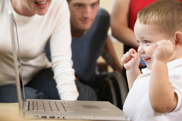 View of a boy smiling in front of the laptop computer.