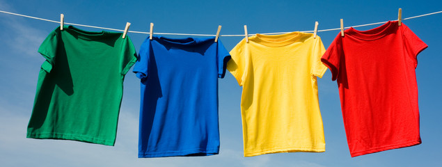 a set of primary colored T-shirts hanging on a clothesline