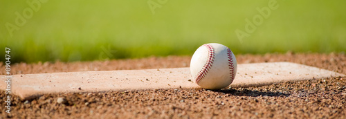 A white leather baseball lying on top of the pitcher's mound