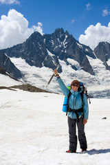 Smiling girl with ice-axe on glacier at Caucasus mountains