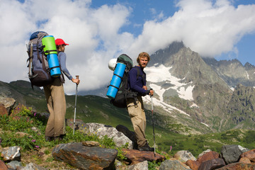 Couple of mountain-climber tourist travelling in high mountains