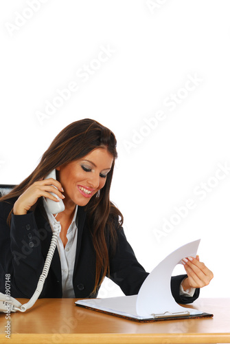 Businesswoman reviewing documents while talking on the phone