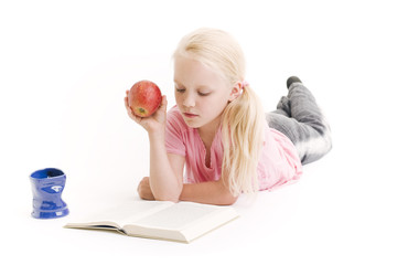 Young girl reading a book and eating an apple