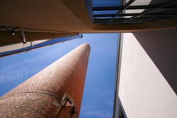 Stillgelegter Fabrikschornstein in Verbindung zu Neubauten