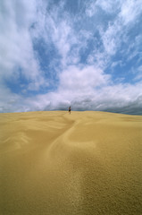 Man in the distance running across sand flats,