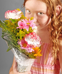 Young girl holding and sniffing bouquet of fresh flowers