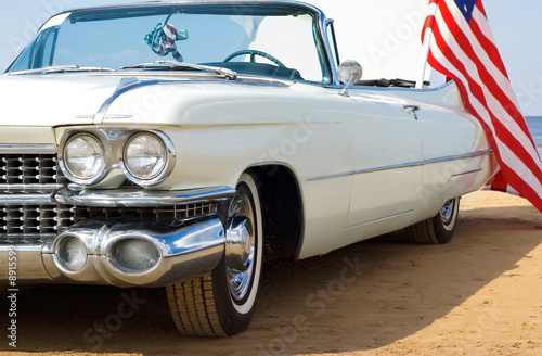Plexiglas Oude auto s Classic white Cadillac at the beach with American flag