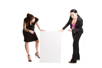 Two businesswomen pointing at a blank billboard
