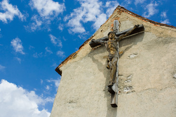 Big wooden cross with sculpted Christ on a building