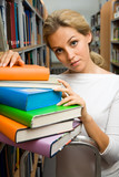 Portrait of smart student touching stack of books in library