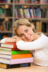 Photo of smiling teacher putting her head over stack of books