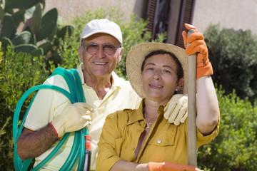 Portrait of senior Italian couple in garden, looking at camera