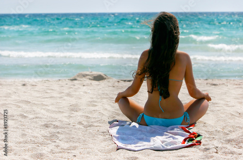 young girl meditating on sand beach