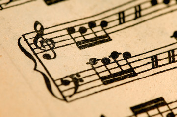 antique music sheet, black notes over worn paper