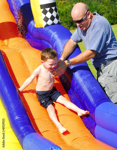 Father helping young son on water slide