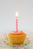Cupcake with candle on glass plate with candy sprinkles poster