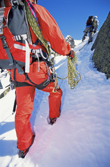 Young men mountain climbing on snowy peak