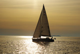 Lonely white sail at infinite ocean on a sunset poster