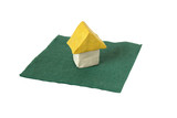 Little plasticine house standing on green paper napkin poster