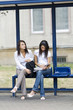 two young and cute brunette waiting for a bus at the bus stop