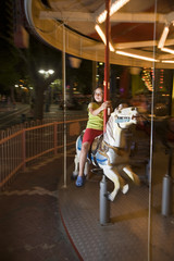 girl on a horse carousel in an amusement park in dusk